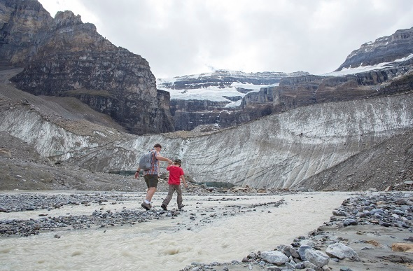 A father and son hiking next to a small rocky river in Banff.