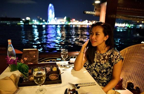 A woman enjoying Thai food on the Anantara cruise.