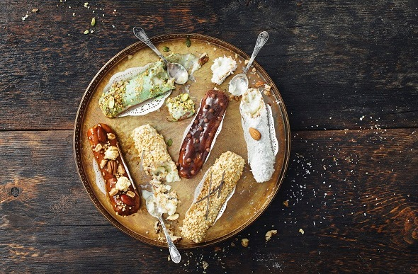 Flat-lay image of chocolate and pistachio eclairs on a gold platter and wooden table.