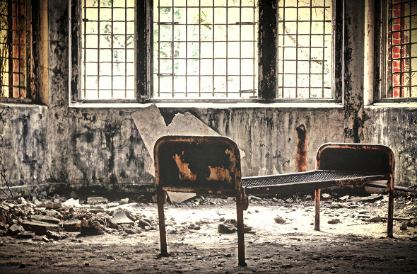 Rusted bed frame in abandoned hospital