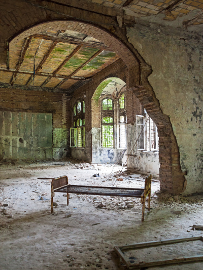 Ruined room with rusted bed in abandoned hospital