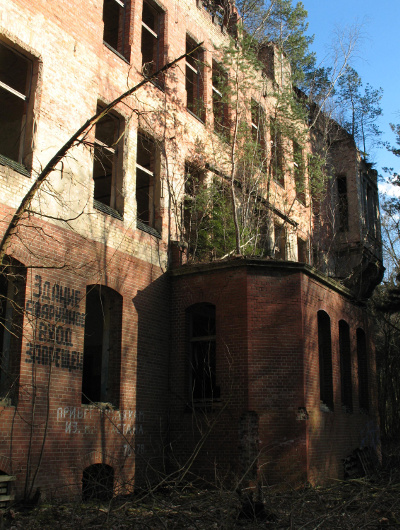 Stained brick exterior of abandoned hospital