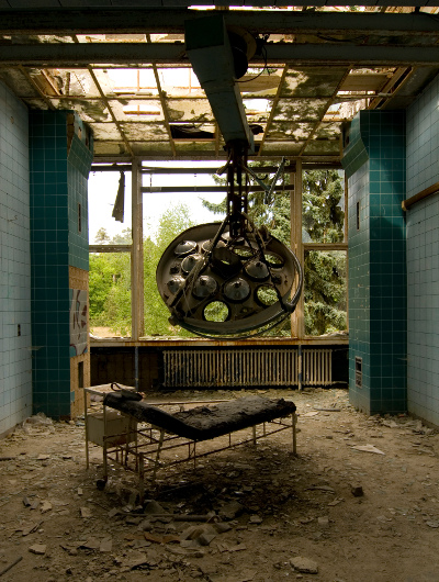 Ruined operating room and equipment in abandoned hospital