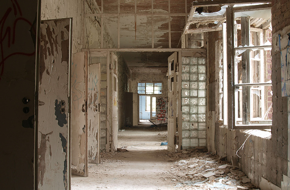 Ruined hall and smashed windows in abandoned hospital