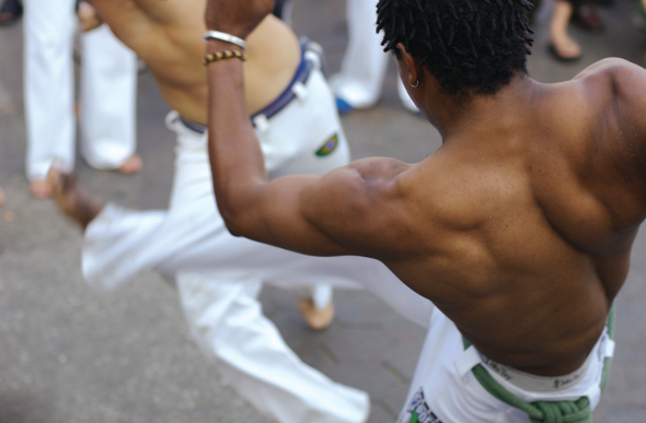 Two muscle-clad Brazilians performing capoeira