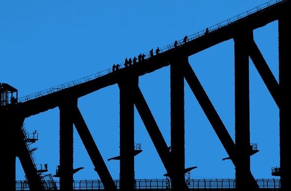 Silhouette of climbers at dawn on the Sydney Bridge Climb.