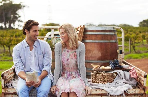A couple sitting on the back of a trailer with a picnic basket and map.