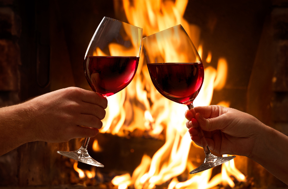 Two wine glasses held in front of a fireplace
