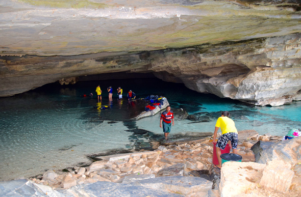 A tour group entering a water-filled cave in swimming gear