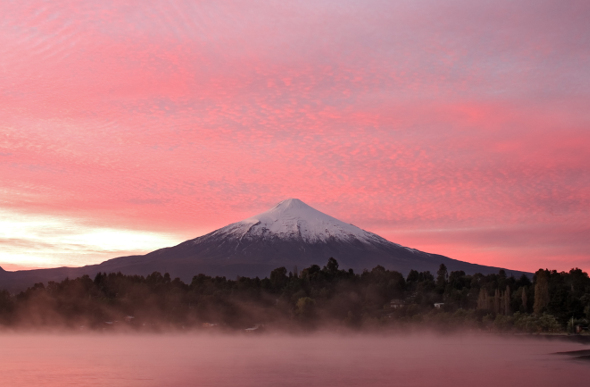 Chile's snow-capped Villarrica Volcano stands against a pink sky as mist rises from the lake in the foreground.
