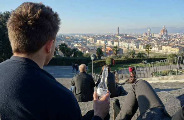 Traveller sitting on steps with beer overlooking Budapest