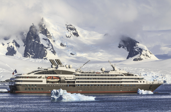 A cruise ship floating past icy mountains in Alaska