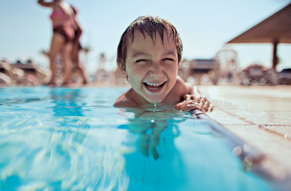 Smiling kid in pool on cruise ship