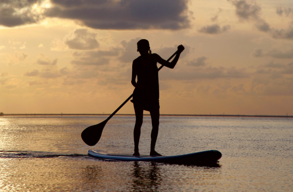 Stand-up paddle boarding during sunset