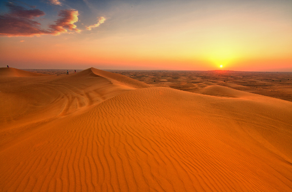 The sun sets over the desert dunes outside Dubai.