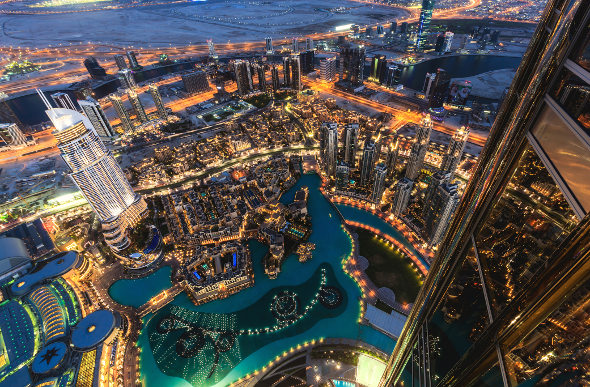 The view of the twinkling lights of Dubai from the Burj Khalifa at night.