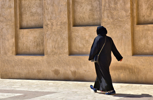 Woman dressed in traditional garb walking past Al-Fahidi in Dubai