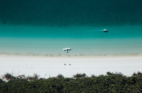 Viewed from the air, a seaplane takes a breather at Whitehaven Beach, as a couple take a picnic on the sands and a boat motors by.
