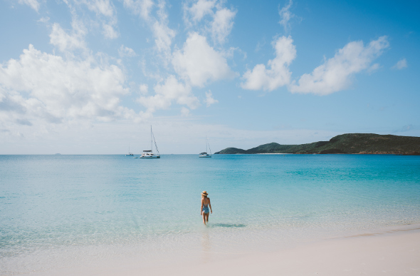 Instagrammer Emilie Ristevski steps into the surreal blue waters of Whitehaven Beach, with moored yachts in the background.