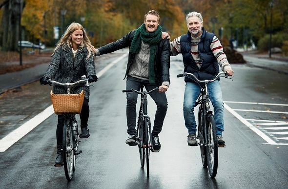Friends cycling on street in Copenhagen, Denmark.