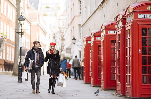A couple walking down the street in London next to a row of telephone boxes.