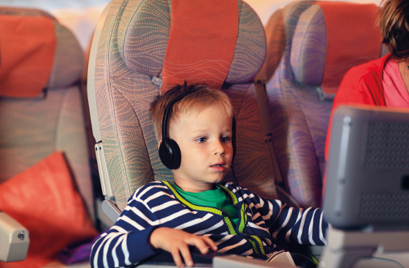 a little boy sitting in an airplane seat