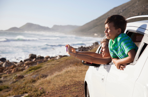 Two kids looking out the window of their car at a beach view