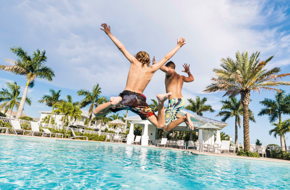 Two young boys jumping into a swimming pool