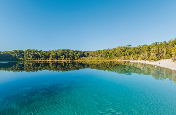 The clear blue waters of Lake McKenzie reflect the sky, as its white-sand beach retreats into the bush on Fraser Island.
