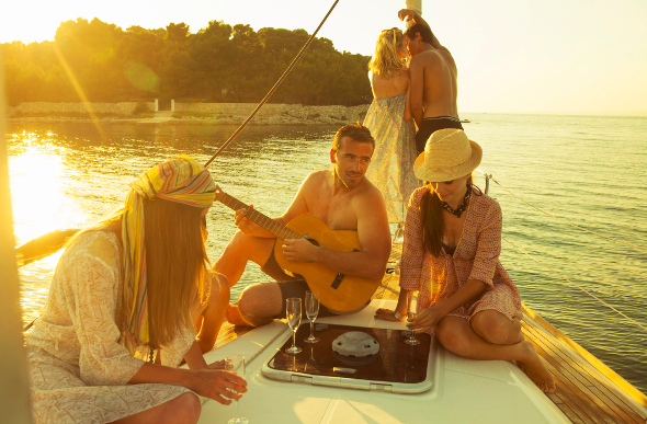 Friends drinking and playing instruments on a yacht in Croatia