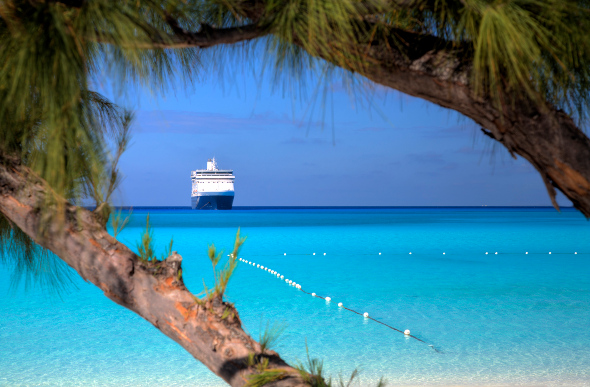 A cruise ship seen from the beach of a tropical island