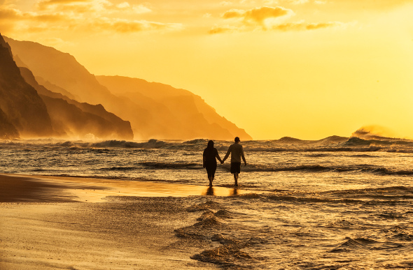 A couple walking along a beach in Hawaii during sunset