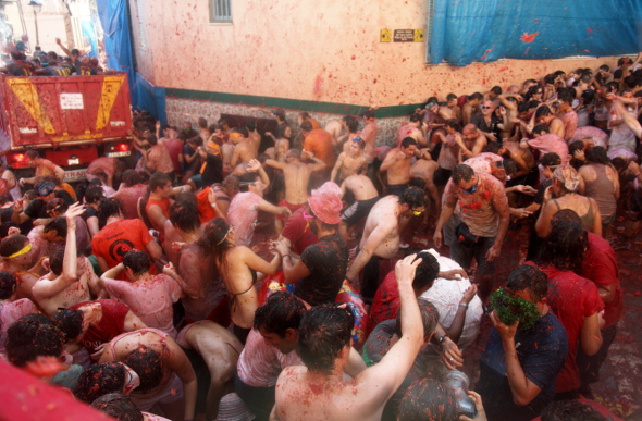 People covered in tomatoes, throwing tomatoes during La Tomatina