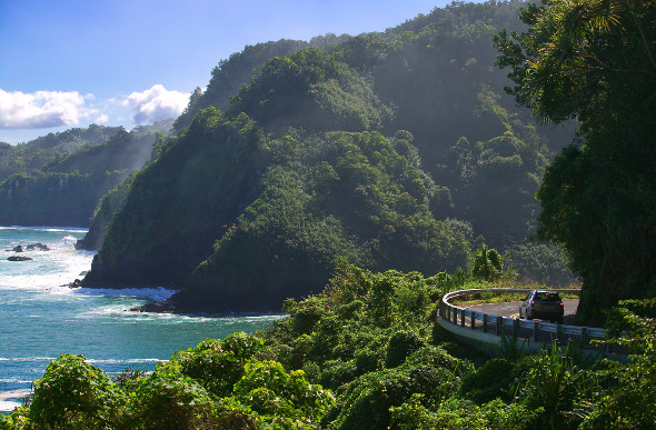 The Road to Hana winds past jungle-covered peaks and crashing ocean waves in Hawaii.