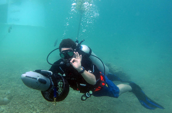 A diver under water with a Seadoo electric dive scooter