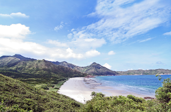 Lush forest meets white sand and blue water at Tai Long Wan beach
