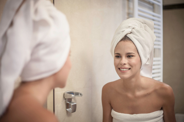 Woman in towel looking in bathroom mirror.