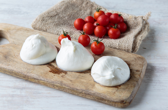 Beautifully presented burrata on wooden board with cherry tomatoes