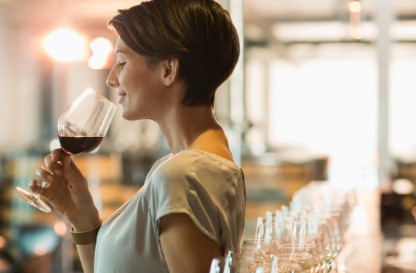 A woman smelling a glass of wine