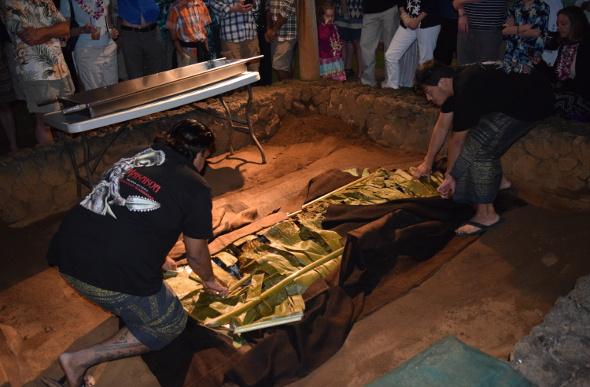 Two men lift food from a traditional earth oven at Kilohana Estate and Plantation on the Hawaiian Island of Kauai.
