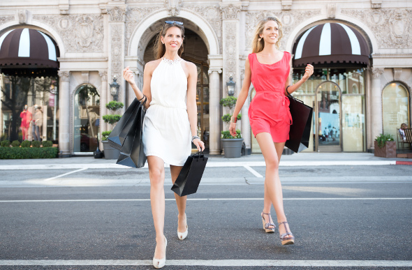 Two women emerge with shopping bags on Rodeo Drive in Los Angeles.