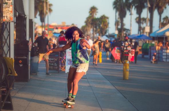 A woman rides a skateboard in Venice Beach, Los Angeles.