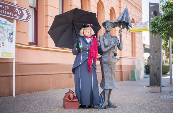 A woman dresses up as Mary Poppins to visit the statue of her creator in Maryborough, Queensland.
