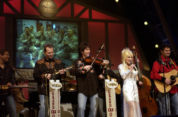 Dolly Parton performing on stage at the Grand Ole Oprey