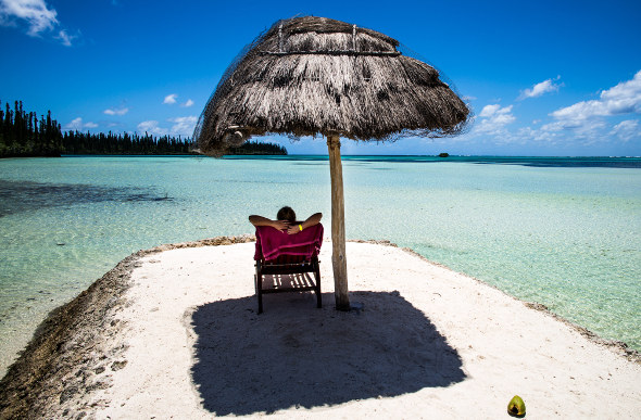 A person sits under a beach umbrella in New Caledonia.