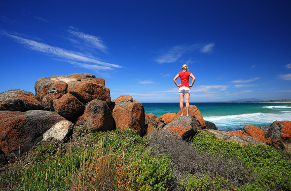 A woman stands on boulders and stares at the sea at Bingie Bingie in New South Wales.