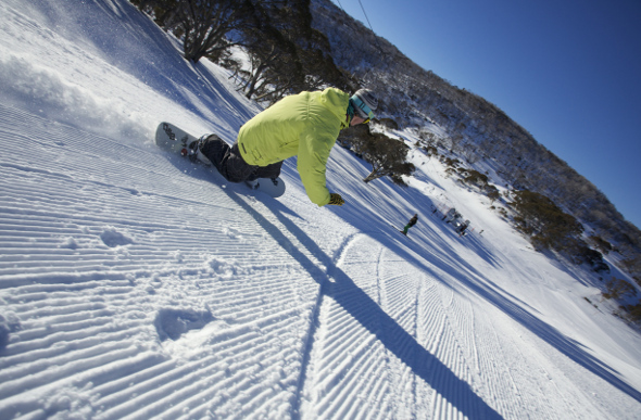 A snowboarding riding down a slop at Perisher