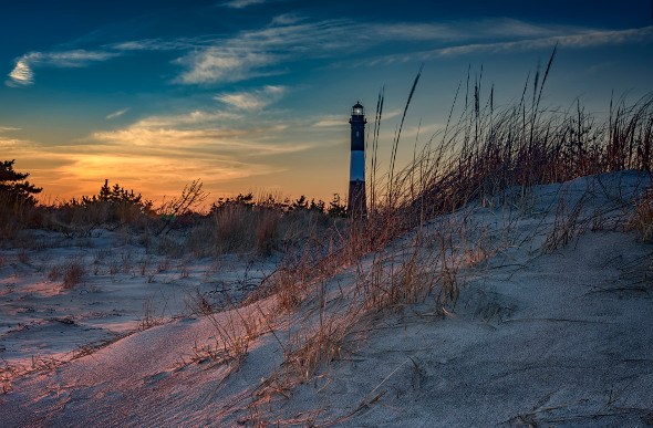 The sun sets behind a lighthouse on Fire Island.