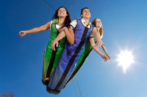 Three people attached together in the swoop full body sling bungee.