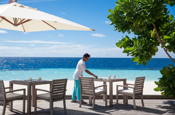 A waiter lays a table at the outdoors Blue Salt restaurant at Outrigger Konotta Maldives Resort
